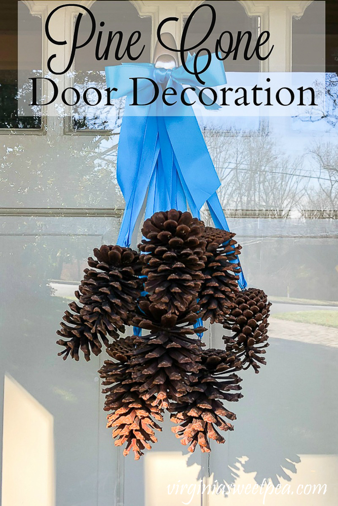 Pine Cone Door Decoration - Learn how to make a beautiful pine cone door decoration that looks lovely on a door for winter.  #winterdoor #winterdoordecoration #pinecone #pineconecraft #pineconewreath  via @spaula