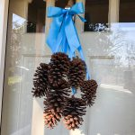 Pine cone door decoration - pine cones hanging from ribbons on a front door.