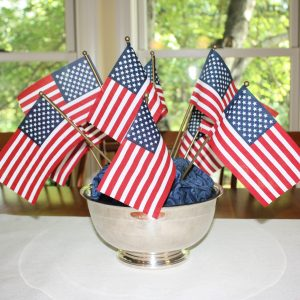 Small American flags displayed in a silver bowl with blue fabric