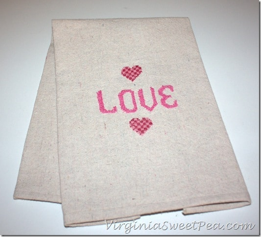 DIY Cross Stitch Valentine's Day Towel - Make this cute tea towel using a drop cloth scrap. It looks so cute hanging on the stove in the kitchen or on display in a bathroom. virginiasweetpea.com #crossstitch #valentinesday #valentinesdaycraft