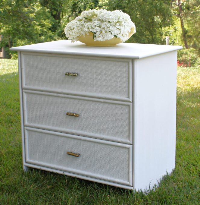 White dresser with wicker look drawers and brass bamboo look pulls.