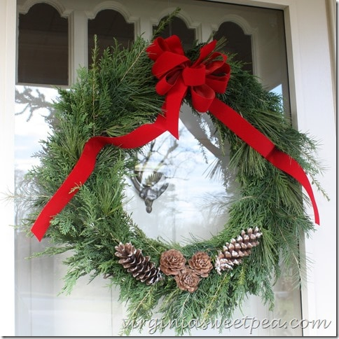 Live greenery wreath made with a variety of pine species and decorated with red ribbon and pine cones.