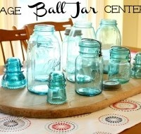 Vintage Ball jars grouped with glass insulators on an antique bread board make a centerpiece that really catches the light.