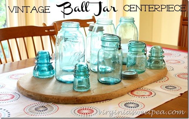 Group vintage ball jars and a few glass insulators on an old bread board to make a centerpiece for your table. virginiasweetpea.com