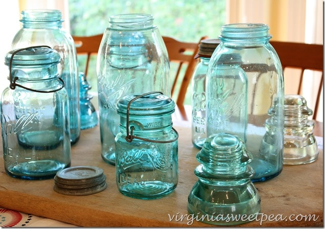 Vintage blue Ball jars and glass insulators used to make a table centerpiece