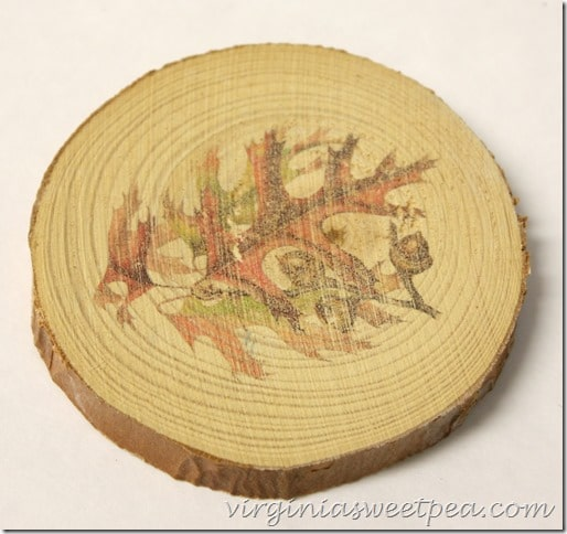 Wood slice with a leaf and acorn image on it.