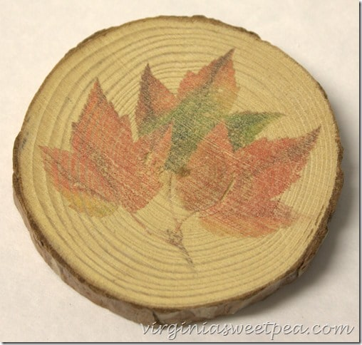 Wood slice made into a coaster with a fall leaf image on it.
