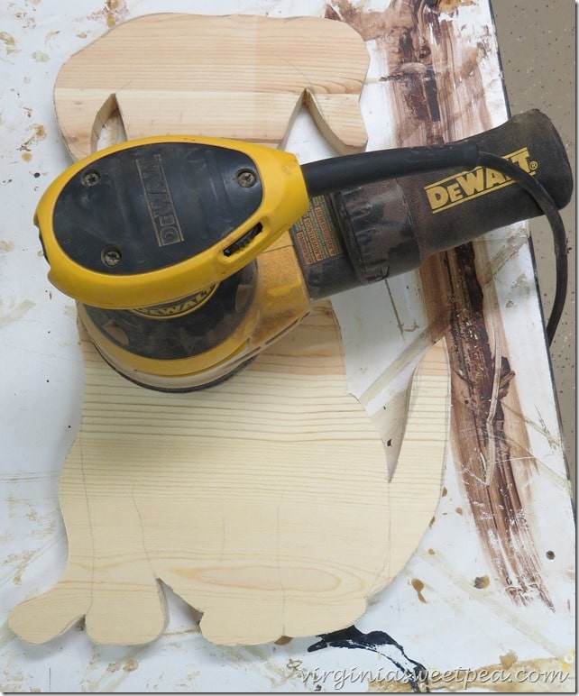 Use a palm sander and regular sandpaper to sand the dog.