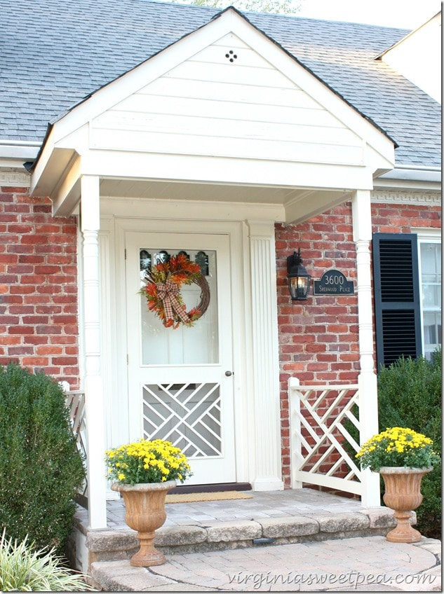 A fall porch with mums and a pretty wreath is a great way to greet guests. virginiasweetpea.com