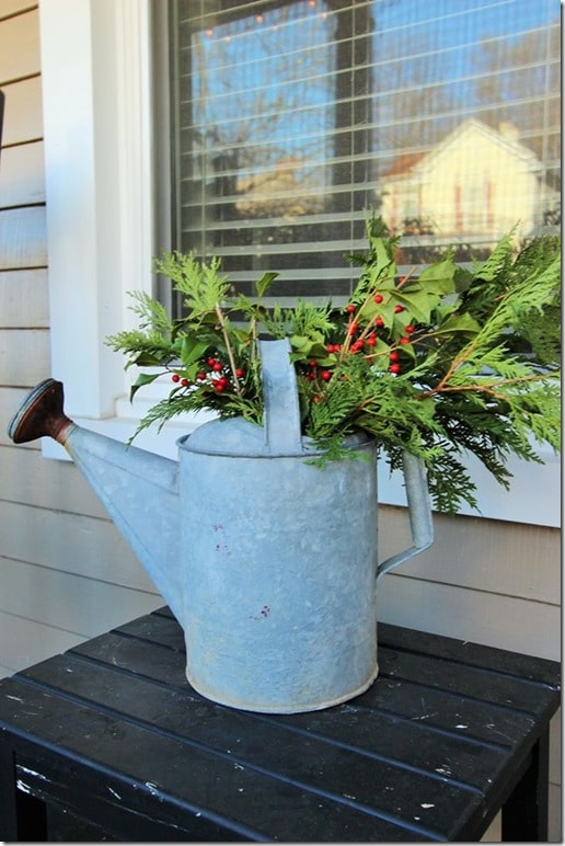 Fresh greenery looks pretty in a watering can as Christmas decor on a porch.
