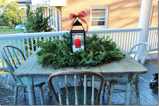 A chippy table and chairs on a porch looks festive for Christmas with a wreath and lantern.
