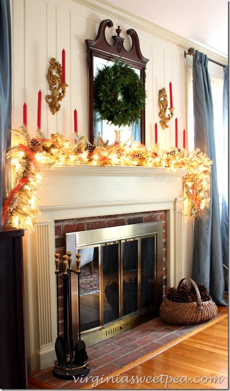 Christmas mantel with a gold lighted garland, red ribbon and candles, and snow covered pine cones. Vintage scones and an antique mirror with a Christmas wreath make this area look so inviting for Christmas.