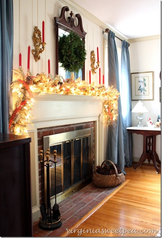 Christmas Mantel for 2015 using lighted garland, snow covered pine cones, and red candles.