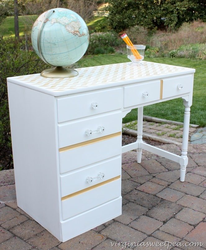 A made over desk with white and gold paint and glass knobs.