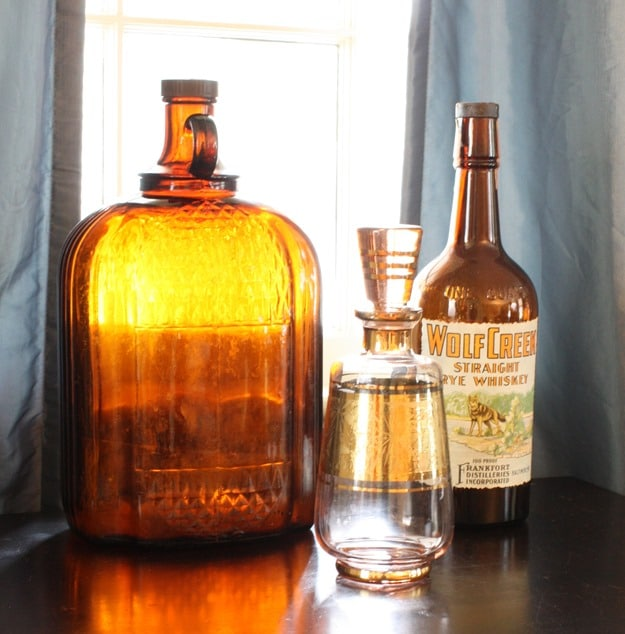 Vintage Brown Clorox Bottle with Wolf Creek Straight Rye Whiskey Bottle and Liquor Decanter I Fall Mantel and Living Room Decor - Get ideas for decorating your mantel and living room for fall. #fall #falldecor #fallvignette #falldecorating #vintage