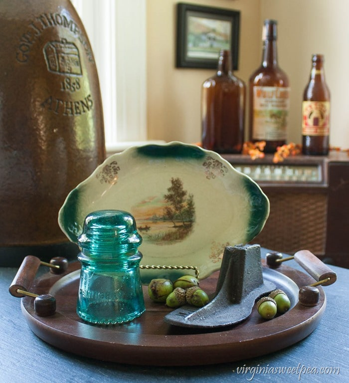 Fall decor with a wooden tray decorated with a small platter with a fall scene, an antique cast iron shoe form, a glass insulator, and in the background three vintage brown bottles.