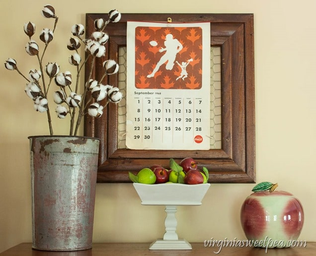 Fall Vignette with a 1968 Coca-Cola Calendar, McCoy Apple Cookie Jar, and Cotton Stems in a Sap Bucket.