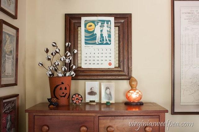 Vintage Inspired Halloween Decor - Vintage toys, old photos, a gourd lamp, and a 1968 Coca-Cola calendar make a fun Halloween vignette. virginiasweetpea.com
