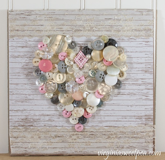 Create art using buttons. This button heart would be pretty to display for Valentine's Day and beyond. It also would make a great gift for a girlfriend. #buttonart #buttonheart #buttoncraft #valentine'sdaycraft