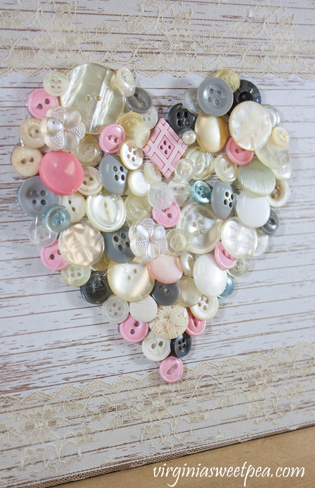 Use buttons to create art like this cute heart. This button heart is perfect for Valentine's Day decor. It's an easy craft that would make a great gift. #valentine'sdaycraft #buttonart #buttoncraft #buttonheart #vintagebuttons