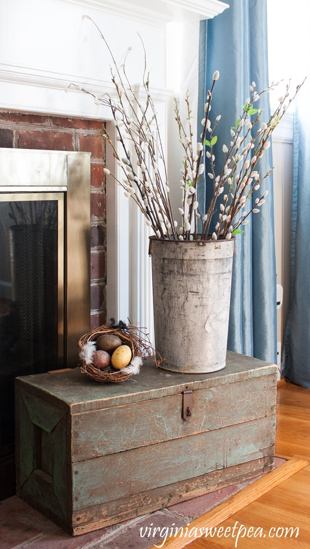 Spring vignette with a vintage tool chest, pussy willow filled sap bucket, and a nest. #spring #springdecor #vintage #vintagedecor