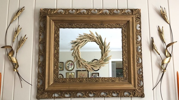 Wheat wreath hanging on a vintage mirror with brash wheat sheaves hanging beside it.