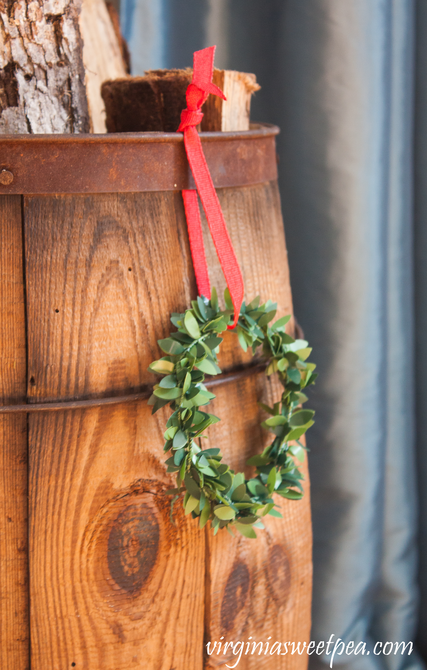 A vintage wooden barrel filled with logs is embellished with a boxwood wreath for Christmas. #christmas #christmashomedecor #christmasideas #favoritechristmasideas #vintagechristmas
