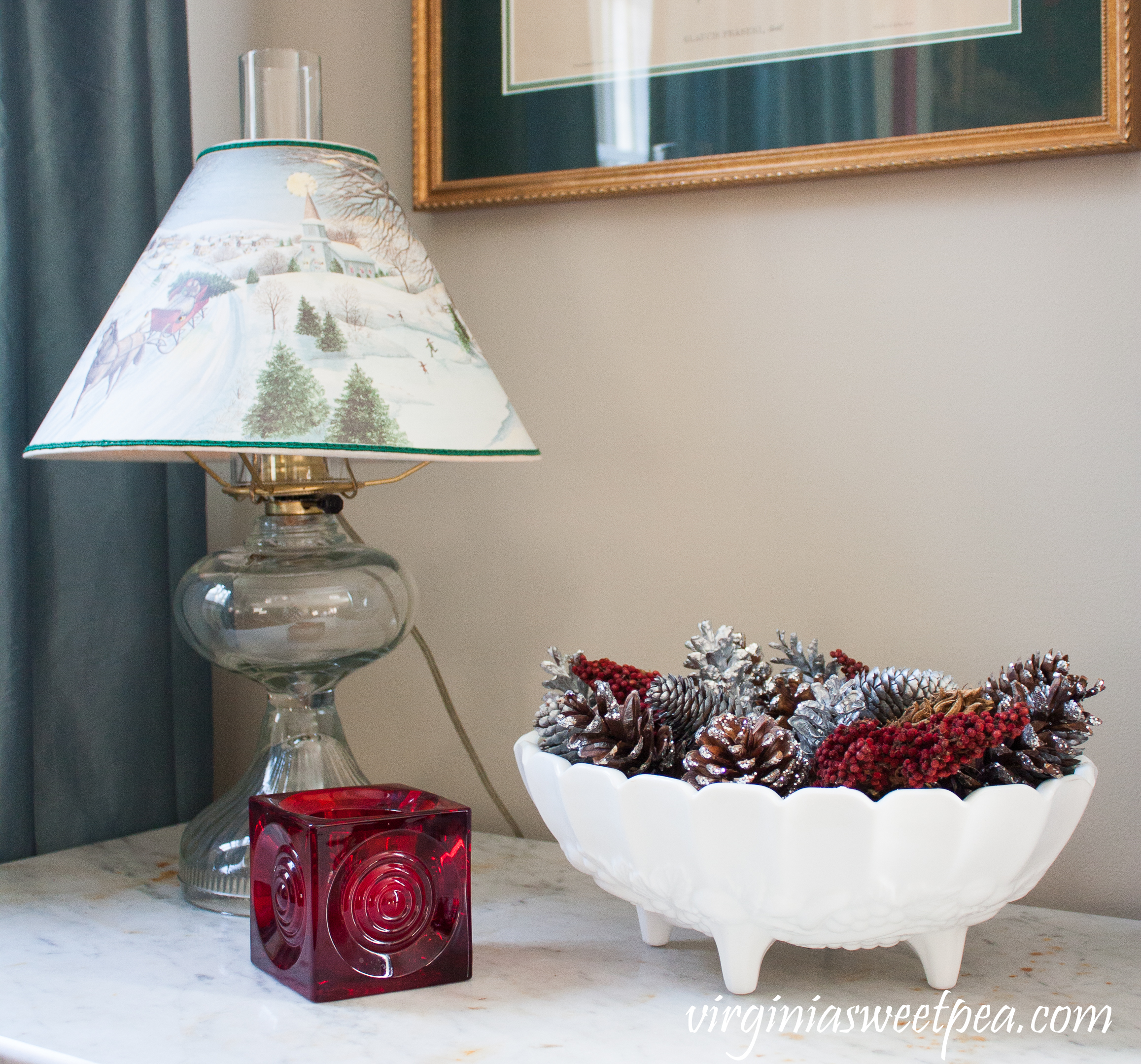 Vintage Christmas Vignette - Antique lamp with a Christmas shade, milk glass compote filled with natural items, and a Blenko candle holder.
