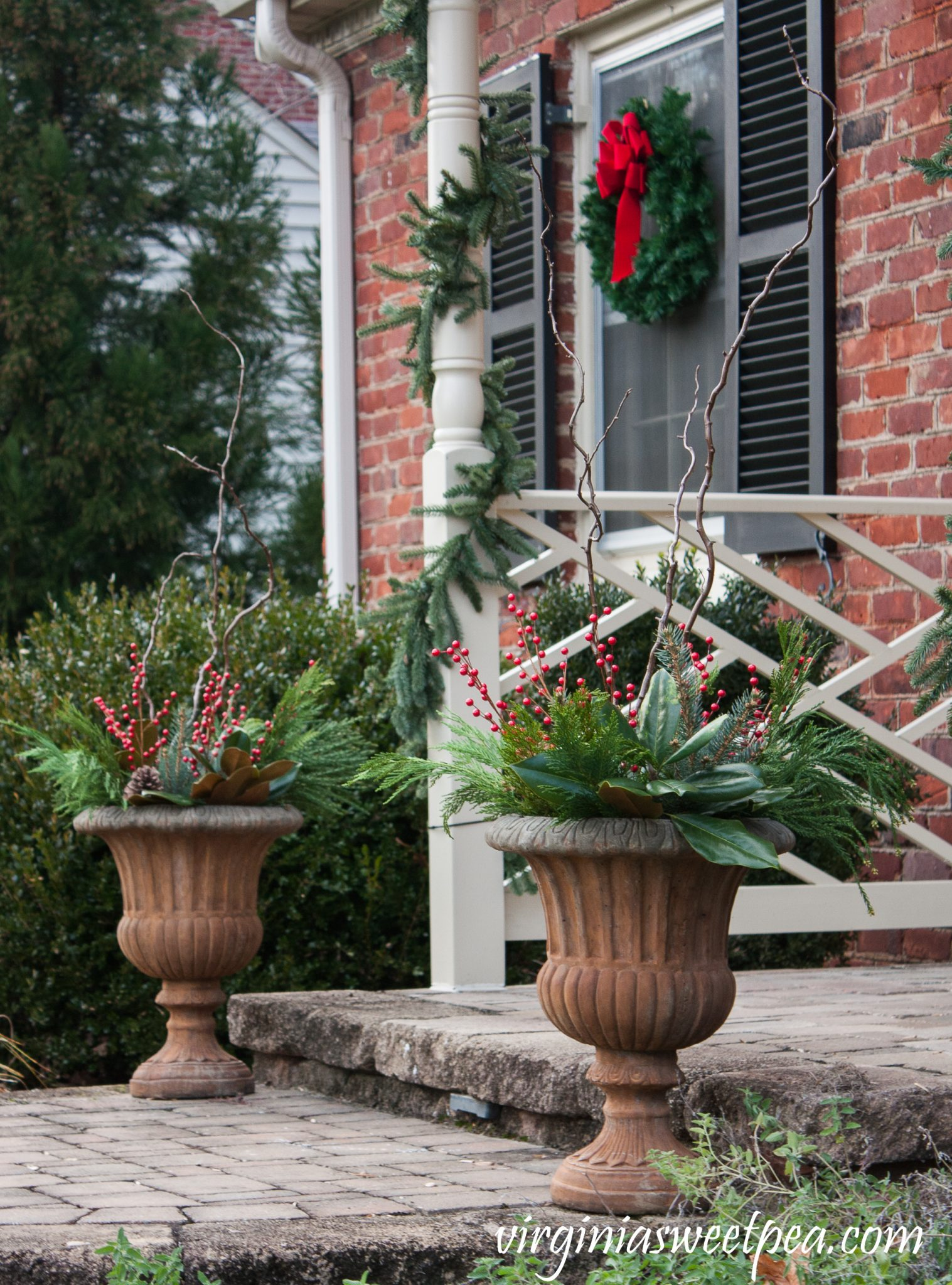 Front porch urns decorated with fresh greenery, curly willow branches and faux berries.