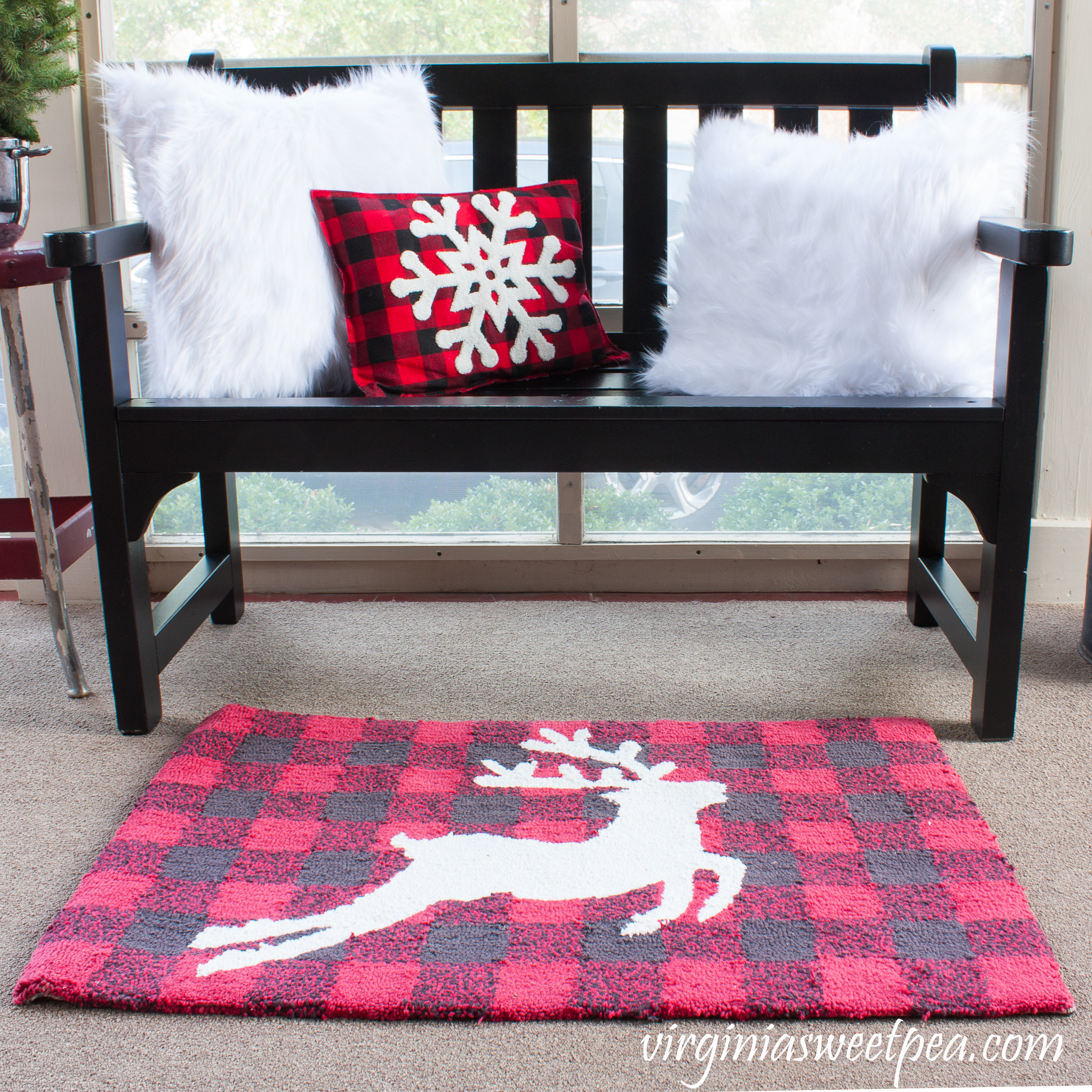 Plow and Hearth bench decorated for Christmas with fur pillow covers, a buffalo check snowflake pillow, and coordinating reindeer rug. #christmas #christmasdecorating #christmasporch