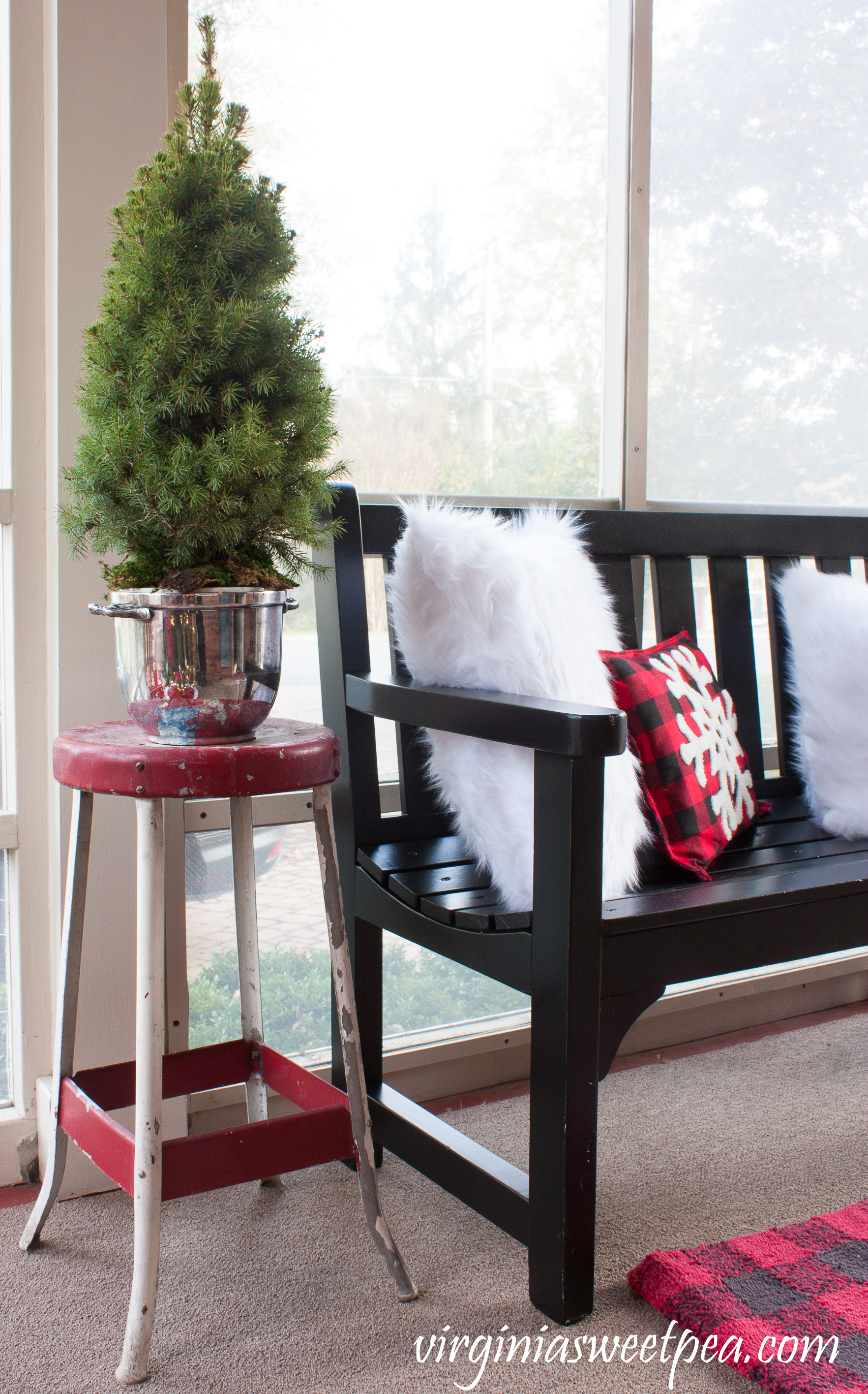 Christmas Porch Decor - A vintage metal stool is topped with a tree planted in a vintage silver ice bucket. #christmas #christmasdecorations #christmasporch #vintage #vintagechristmas