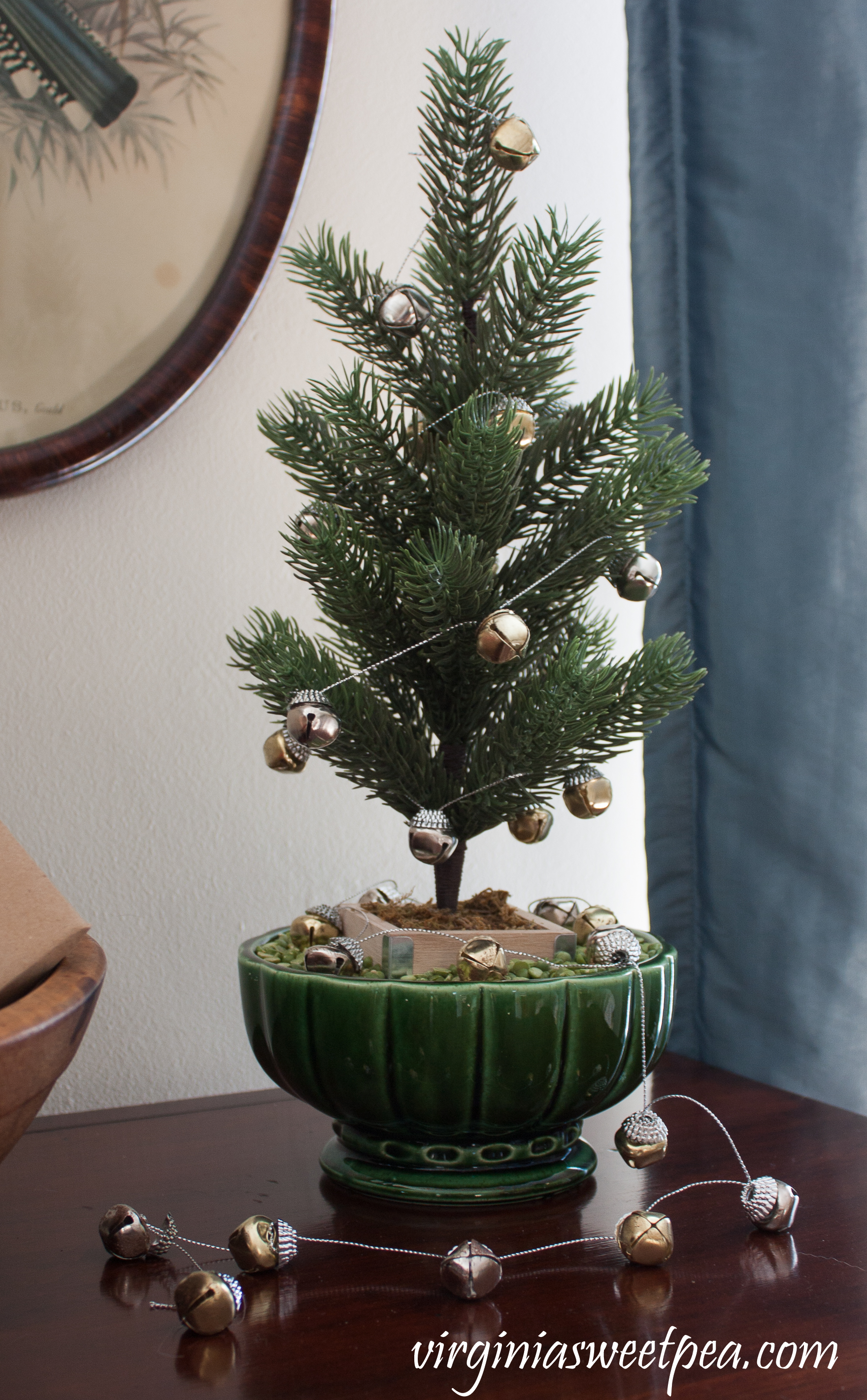 "Christmas Home Tour - A small tree is ""planted"" in a vintage planter with split peas used for soil and decorated with a bell garland. #christmas #christmastree #christmasdecorations"