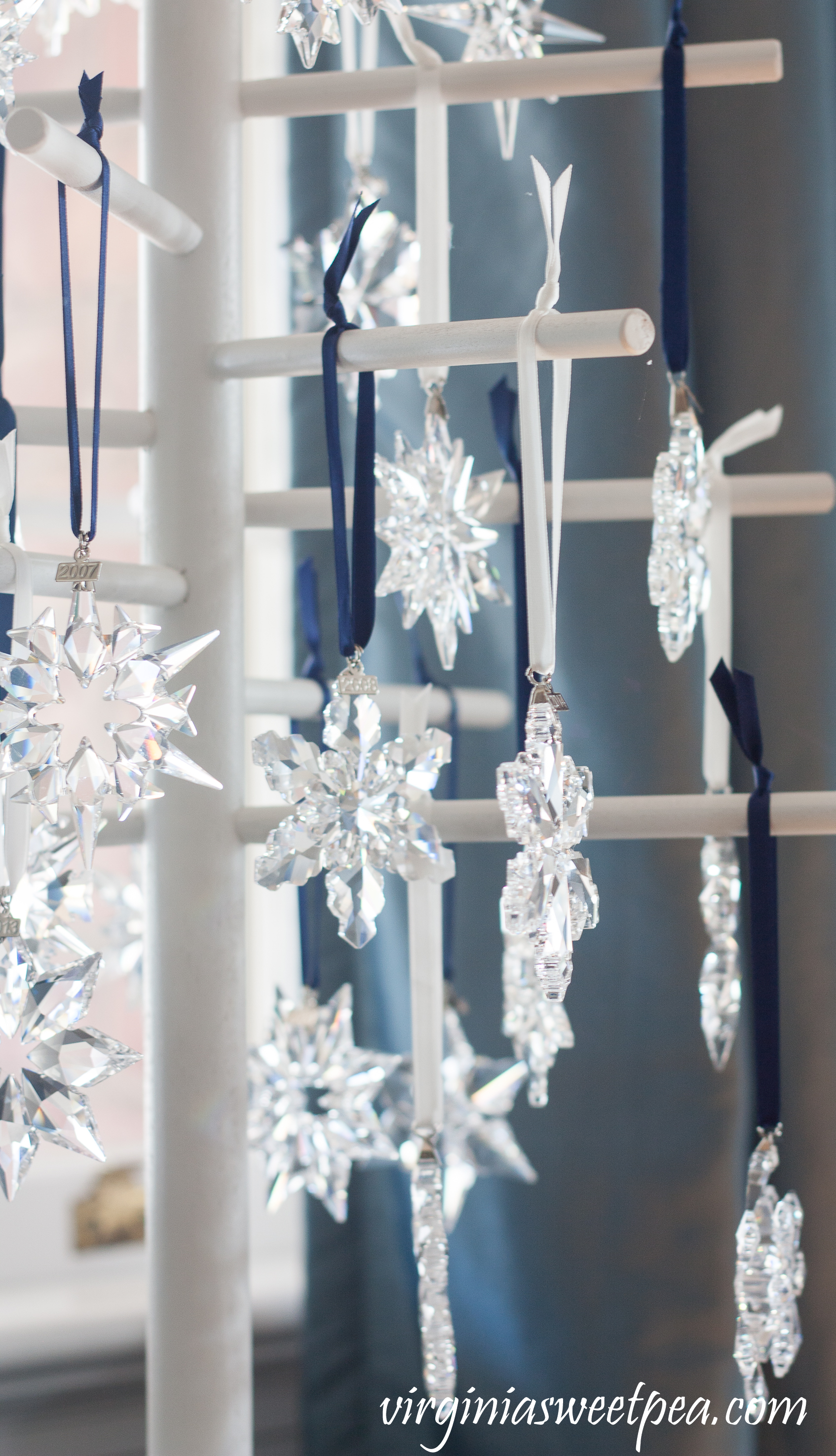 Swarovski Snowflake Ornaments - A collection of snowflakes from 1994 - 2018 is displayed on a wooden tree. #swarovski #swarovskiornaments #swarovskisnowflakeornaments