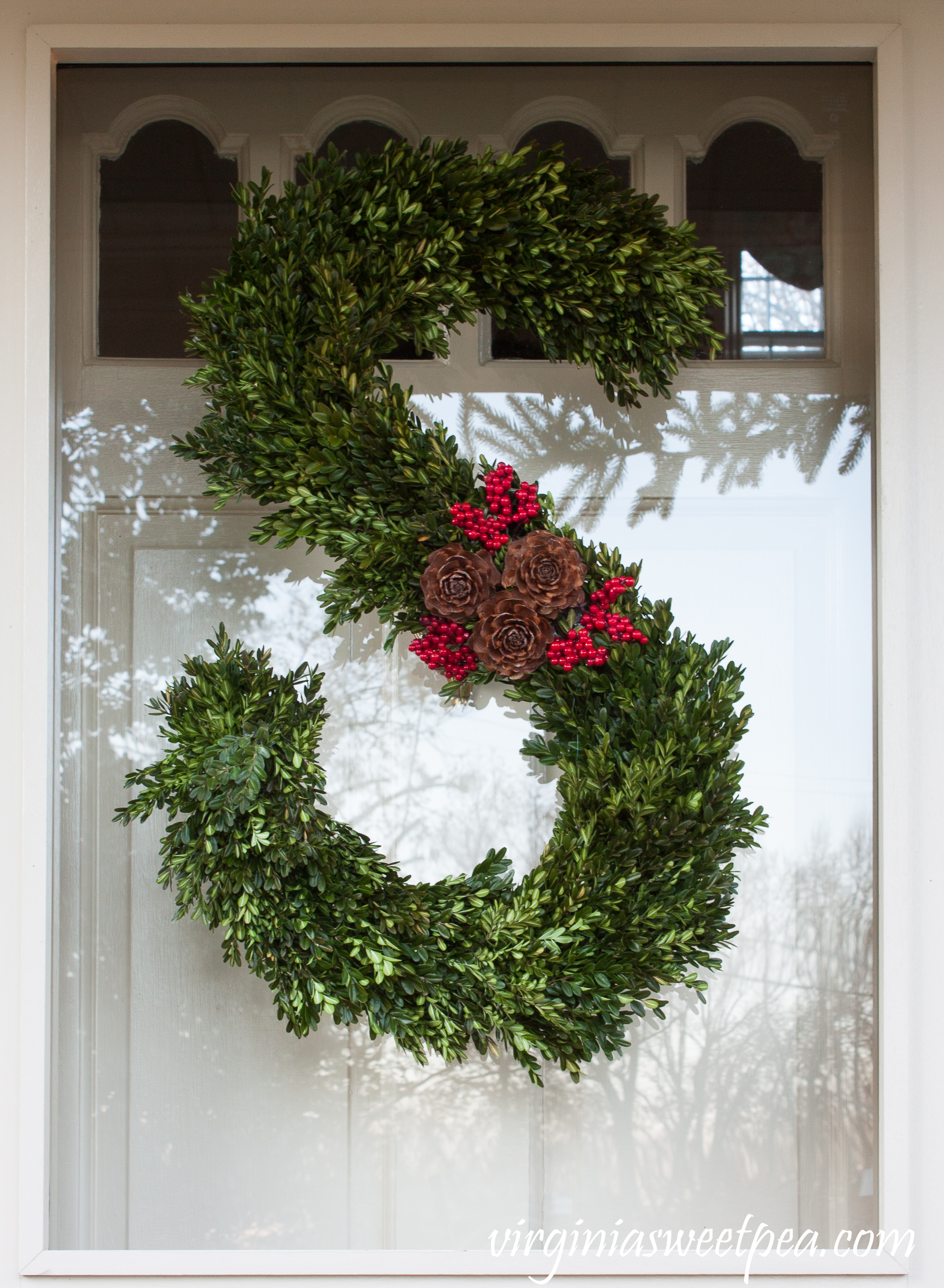 Front porch decorated for Christmas with a handmade monogram wreath decorated with boxwood, berries, and pinecones.