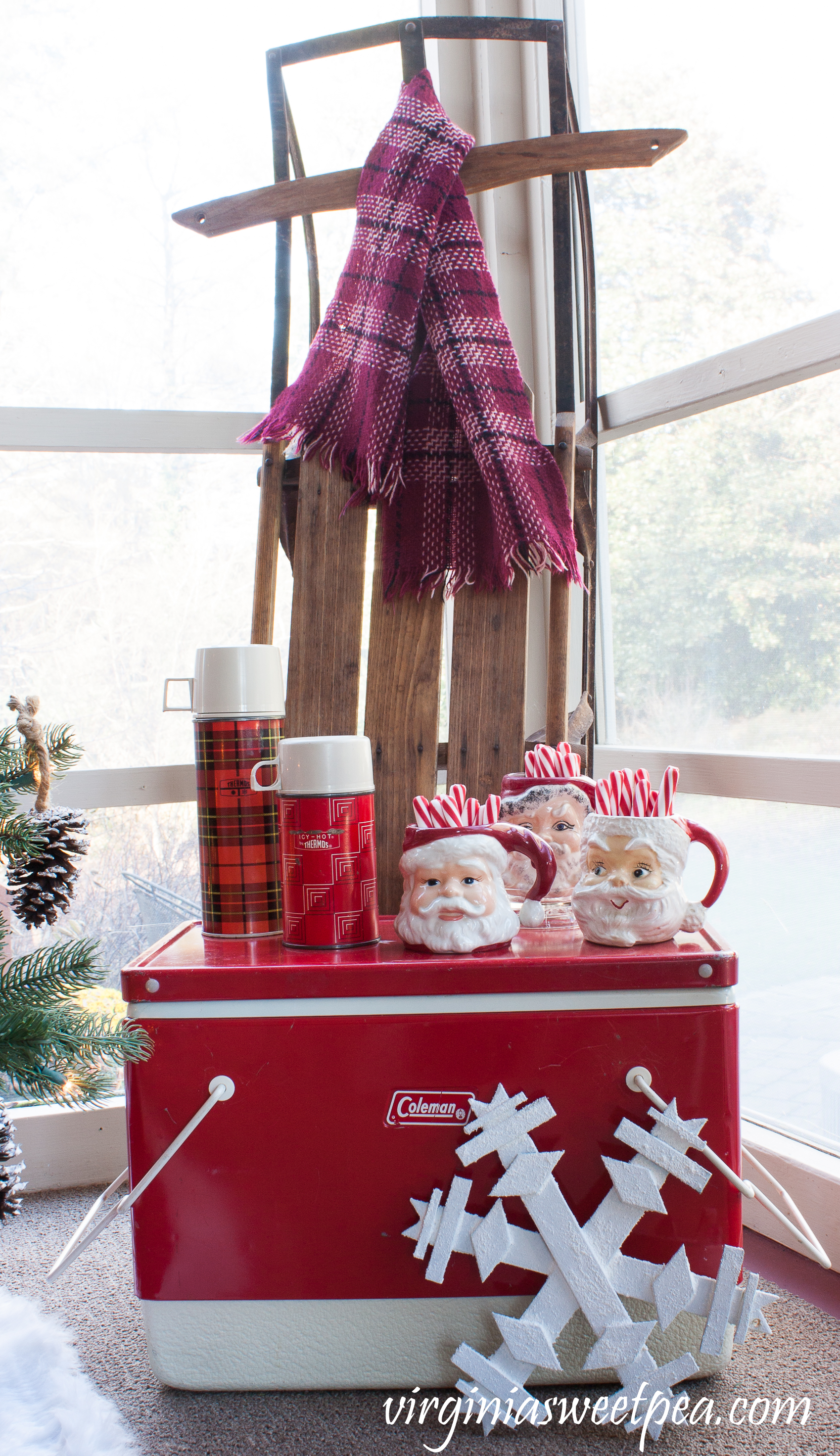 Christmas Porch Vignette - A vintage Coleman cooler is topped with vintage thermoses and Santa mugs. A vintage sled is adorned with a vintage scarf. #christmas #christmasdecorations #christmasporch #vintage #vintagechristmas