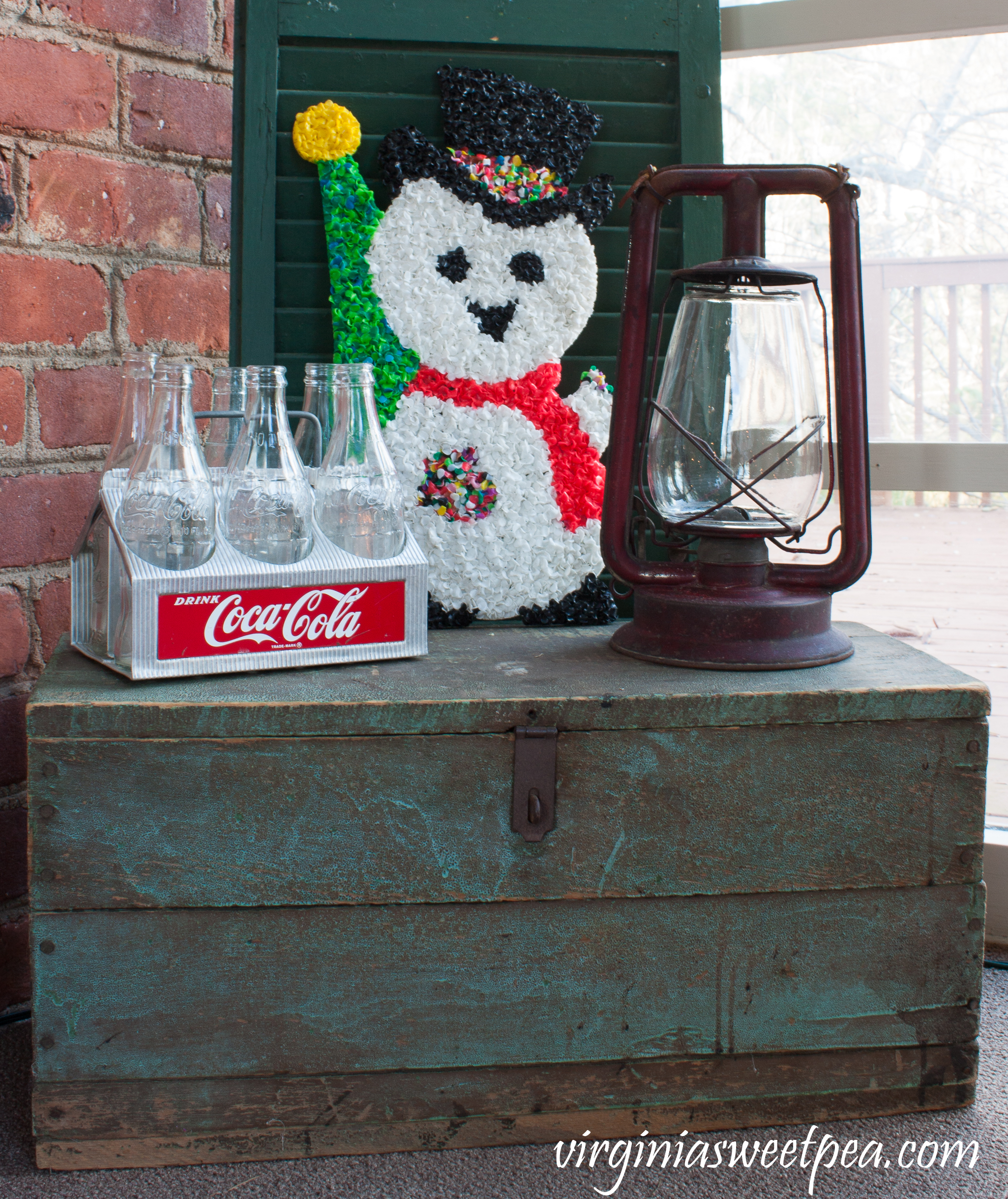Vintage Christmas Vignette - A Coke caddy, 1970's plastic snowman door decor, and an antique lantern are displayed on a an antique tool chest. #christmas #christmasdecorations #christmastree #christmasporch #vintagechristmas #cocacola