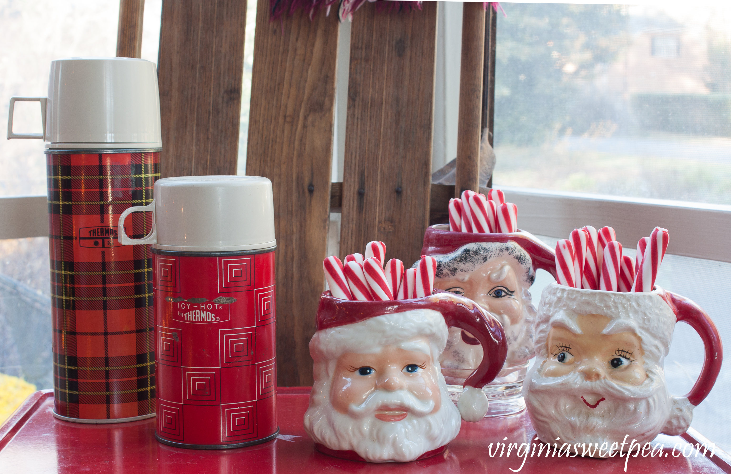 Christmas Porch Vignette - Vintage thermoses with Santa mugs. #christmas #christmasdecorations #christmasporch #vintage #vintagechristmas