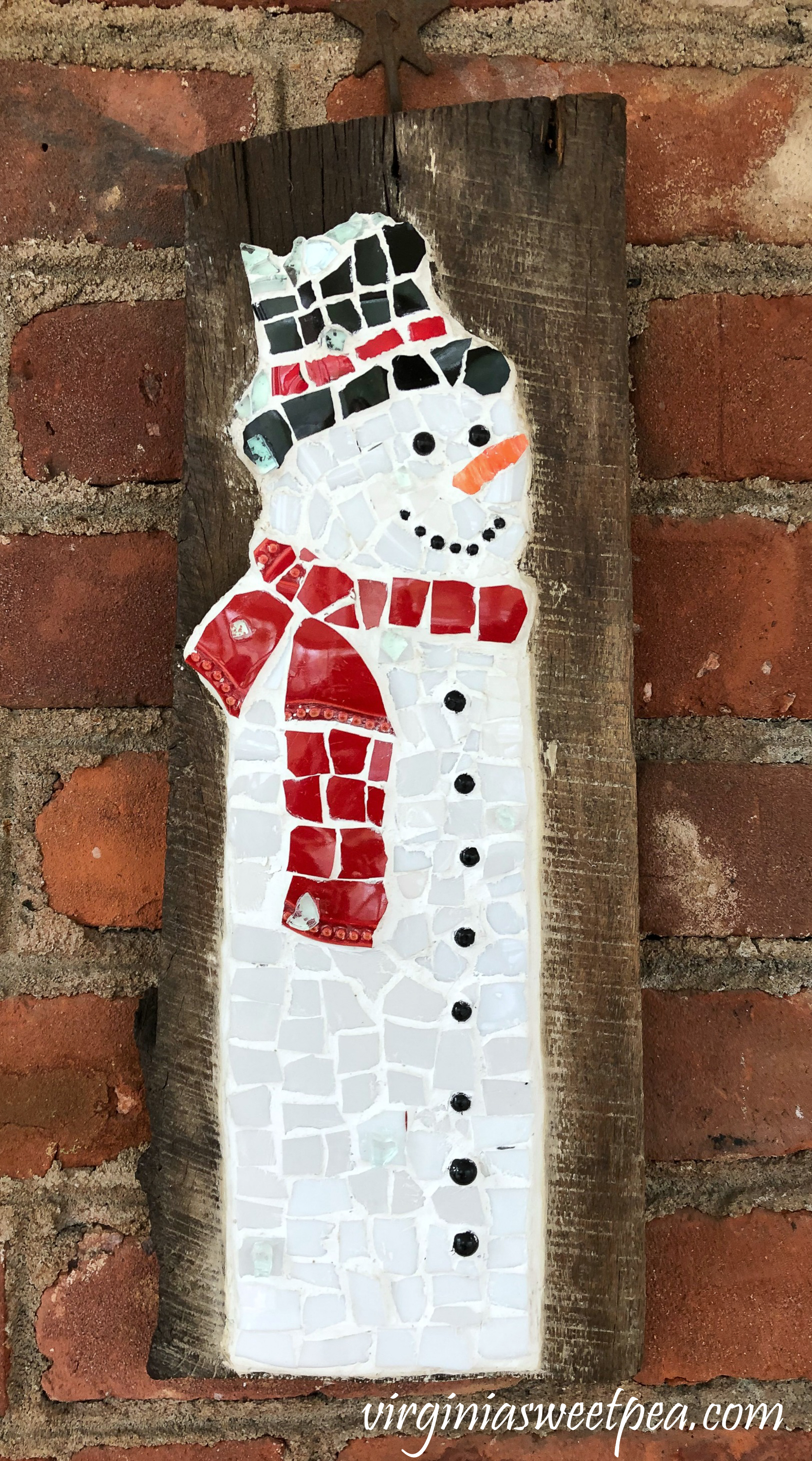 Snowman made with dish pieces on a piece of barnwood.