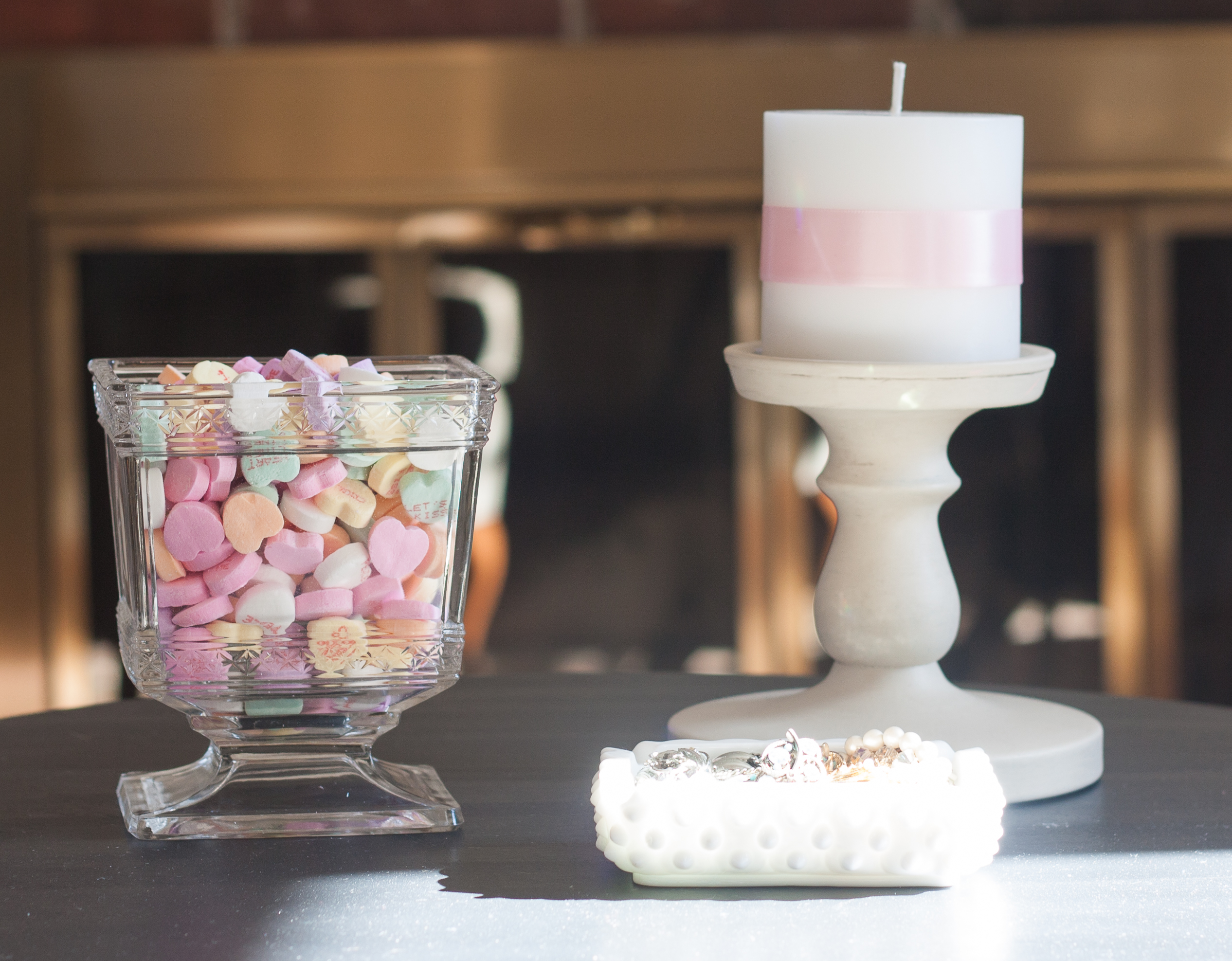 Valentine's Day Vignette with Conversation Hearts in an antique glass vase; vintage costume jewelry in a milk glass ashtray; and a candle made romantic with the addition of pink ribbon. #valentinesday #valentinesdayvignette #valentinesdaydecor #conversationhearts #milkglass