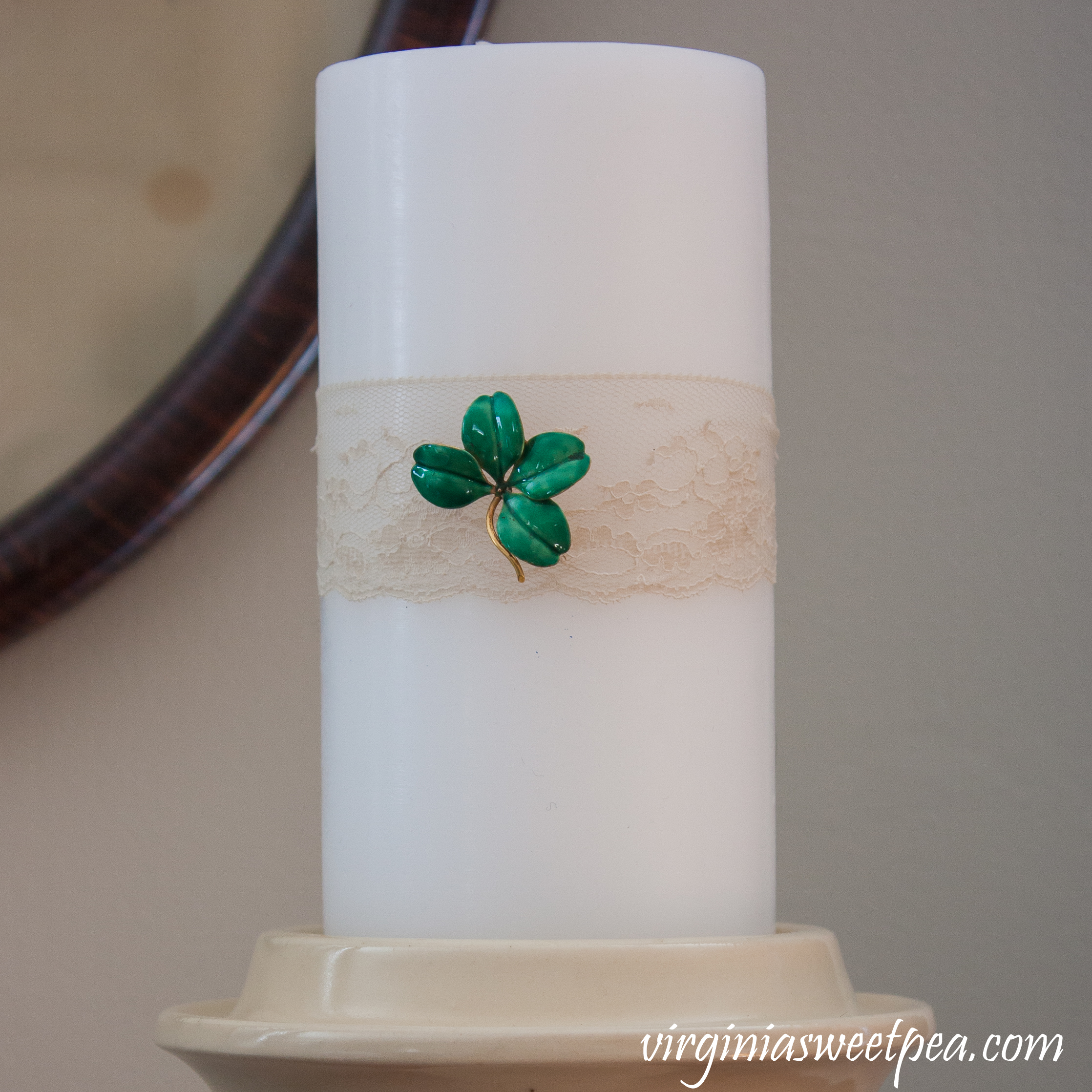 Candle decorated for St. Patrick's Day with lace and a vintage four leaf clover pin. #stpatricksdaydecor #vintagejewelry #fourleafcloverpin