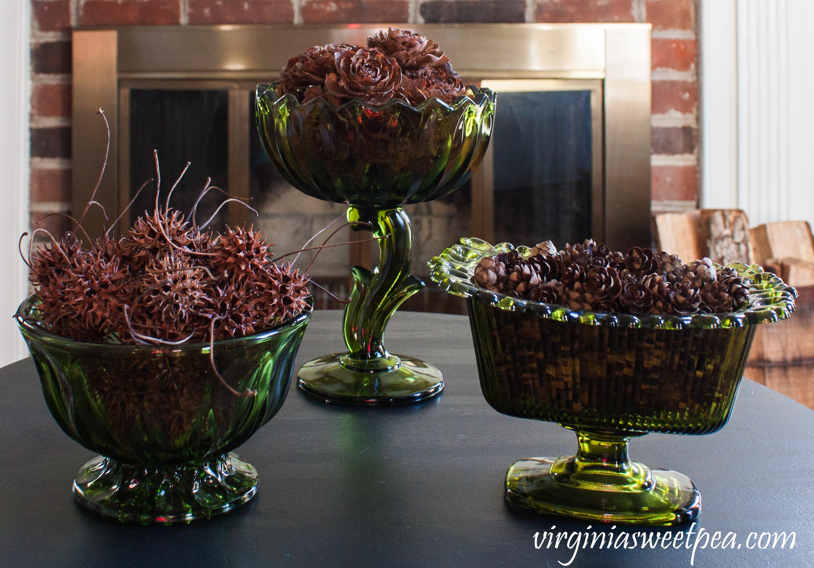 Three vintage green vases are filled with items from nature including Deodora Cedar cones, Hemlock cones, and Sweet Gum seed pods. #vintagegreenglass #deodoracedar #hemlockcone #sweetgumtree