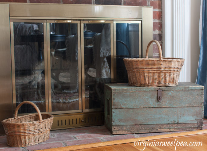 Vintage Baskets used on a fireplace hearth with a vintage toolbox