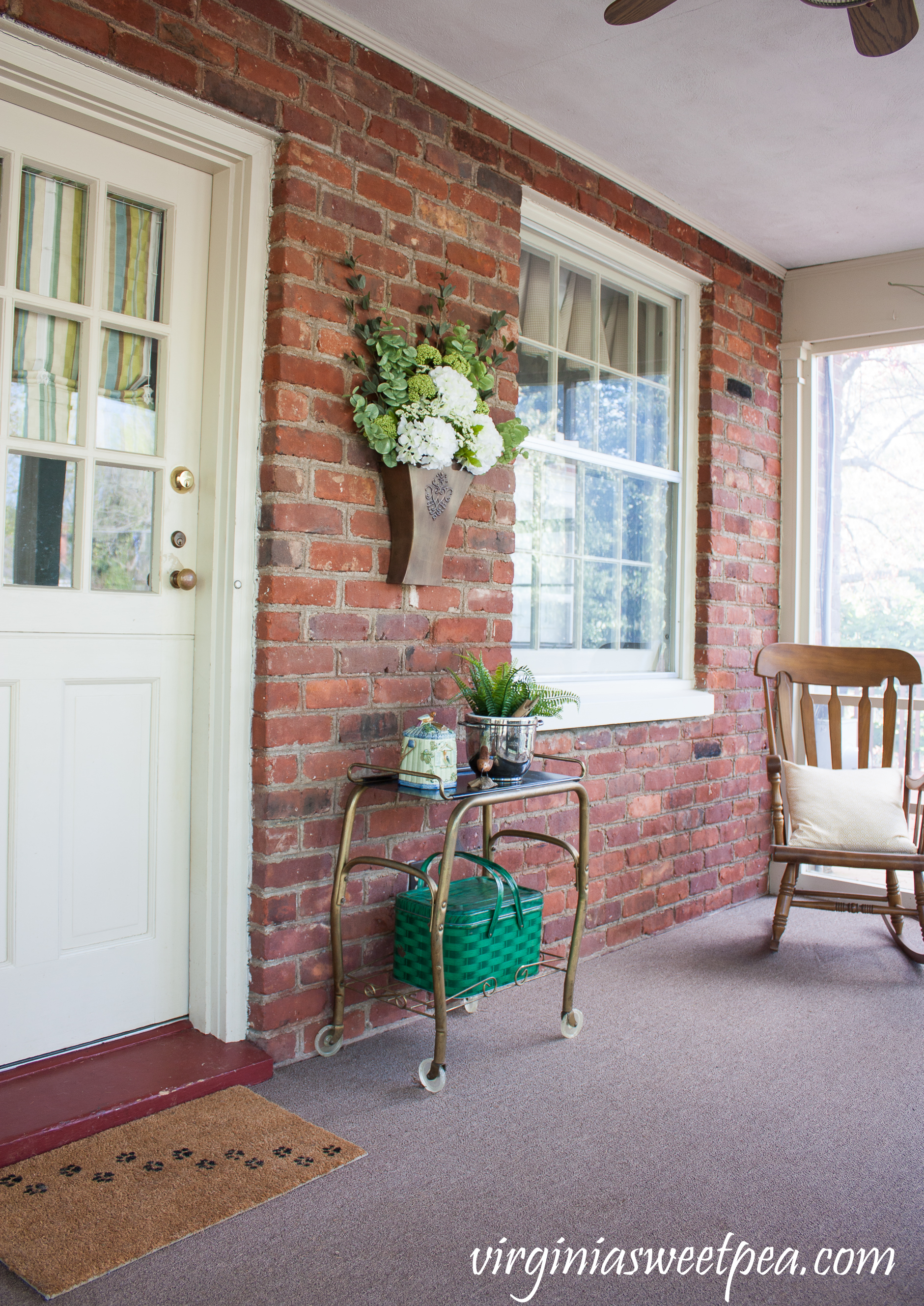 Spring on the porch with a hanging flower arrangement in a Southern Living at Home Willow House Flower Market Door Bucket