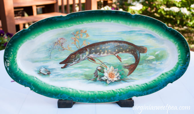 Antique fish platter displayed using a DIY wood display stand.