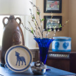 Easter vignette with a Blue Ridge Pottery lamb plate, Blenko blue vase, and a silver child's porridge bowl with a nest.