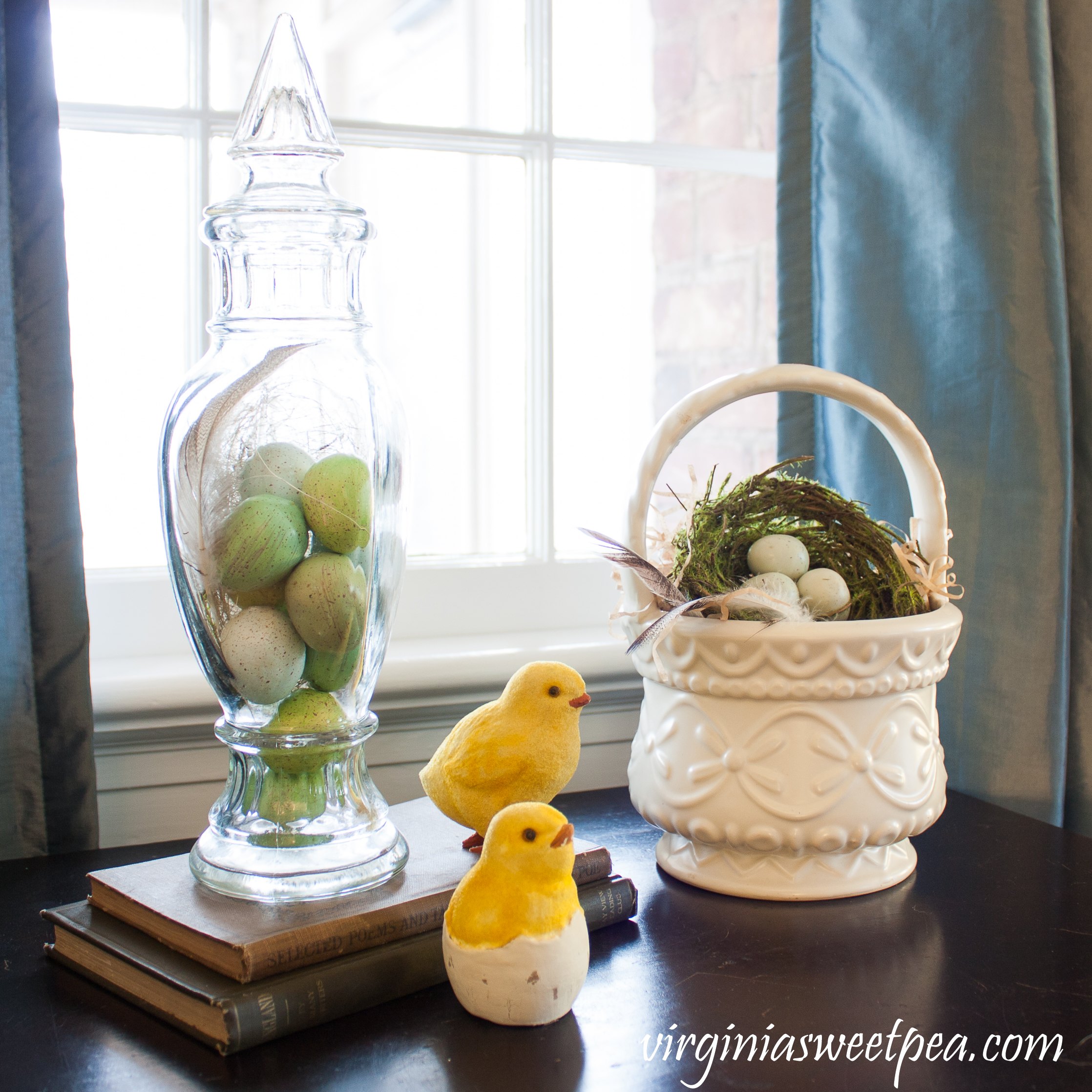 Easter vignette with eggs in a vintage glass candy holder, a nest in a Hull basket, chicks, and antique books #easterdecor #easterdecorations #vintagedecor #hull