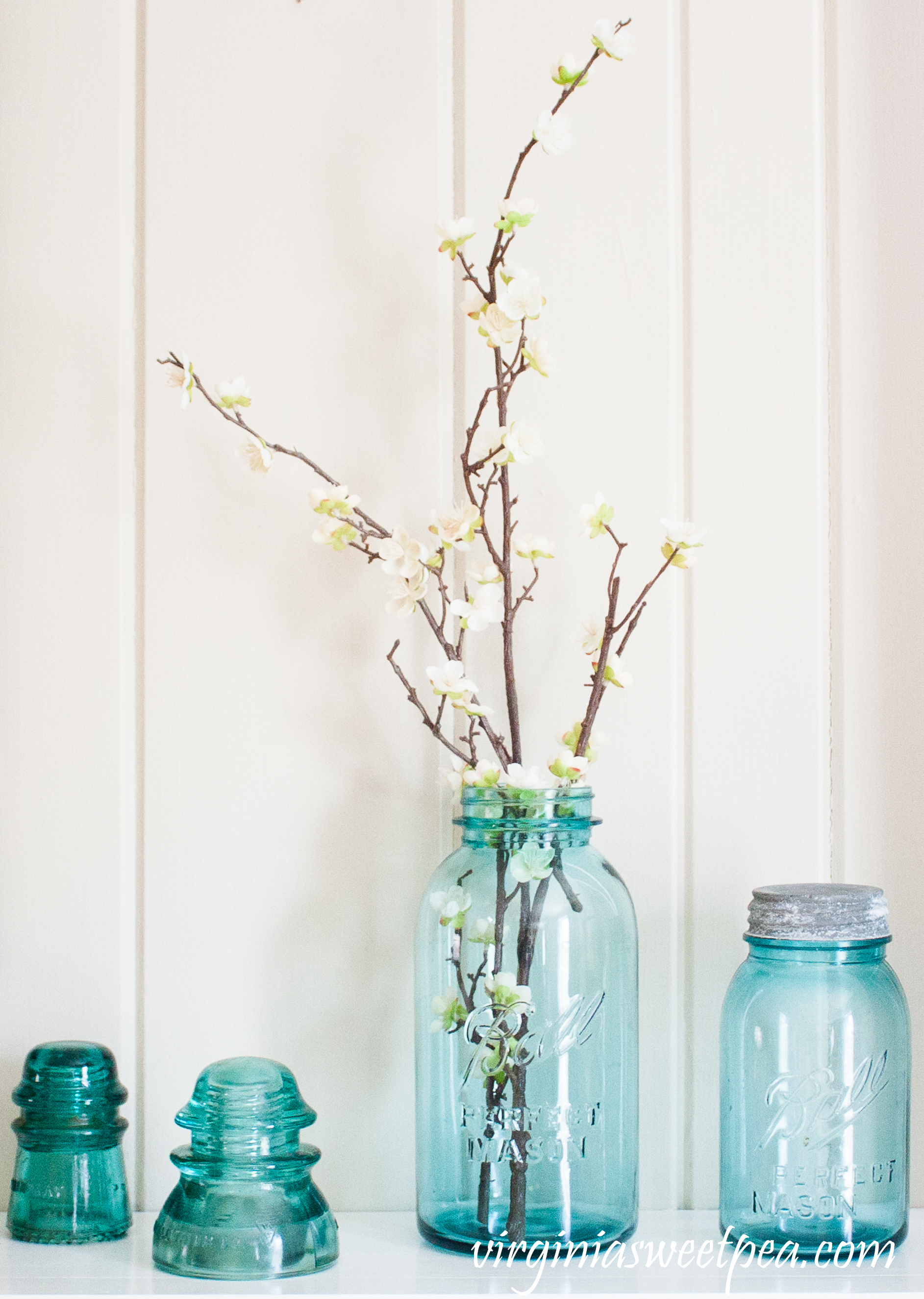 Vintage Blue Ball Jars and Insulators used on a Spring Mantel - #springmantel #springdecor #vintage #vintagedecor #balljars