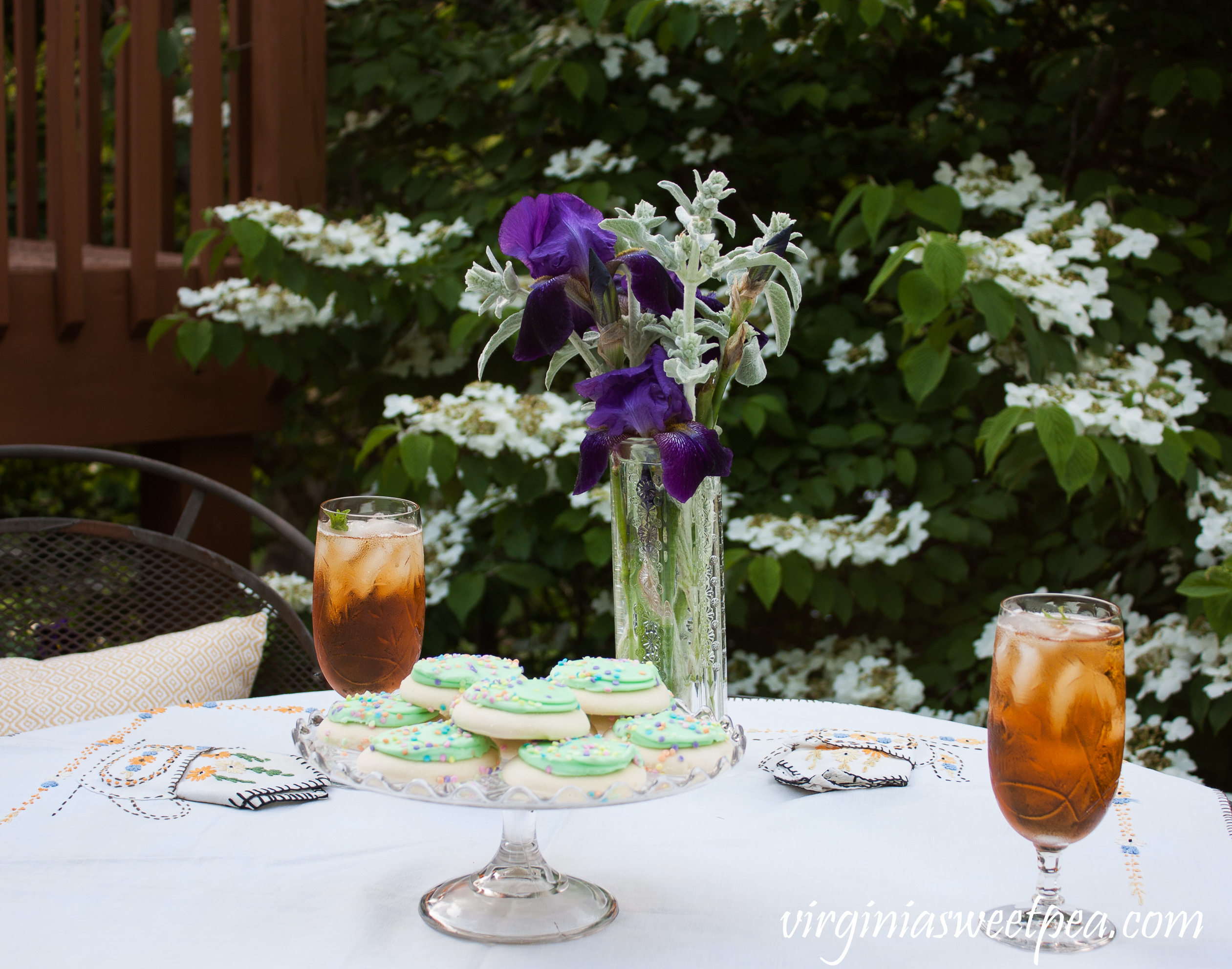 A Tea Party Featuring a 1930's Tea Themed Embroidered Tablecloth and vintage cake server, crystal, and flower vase.