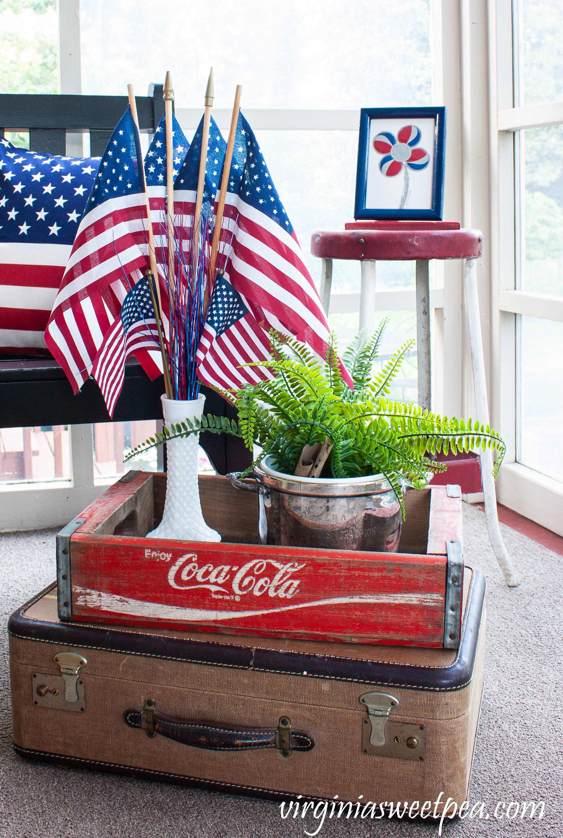 Patriotic display with a Coke crate, vintage suitcase, and milk glass vase filled with flags.