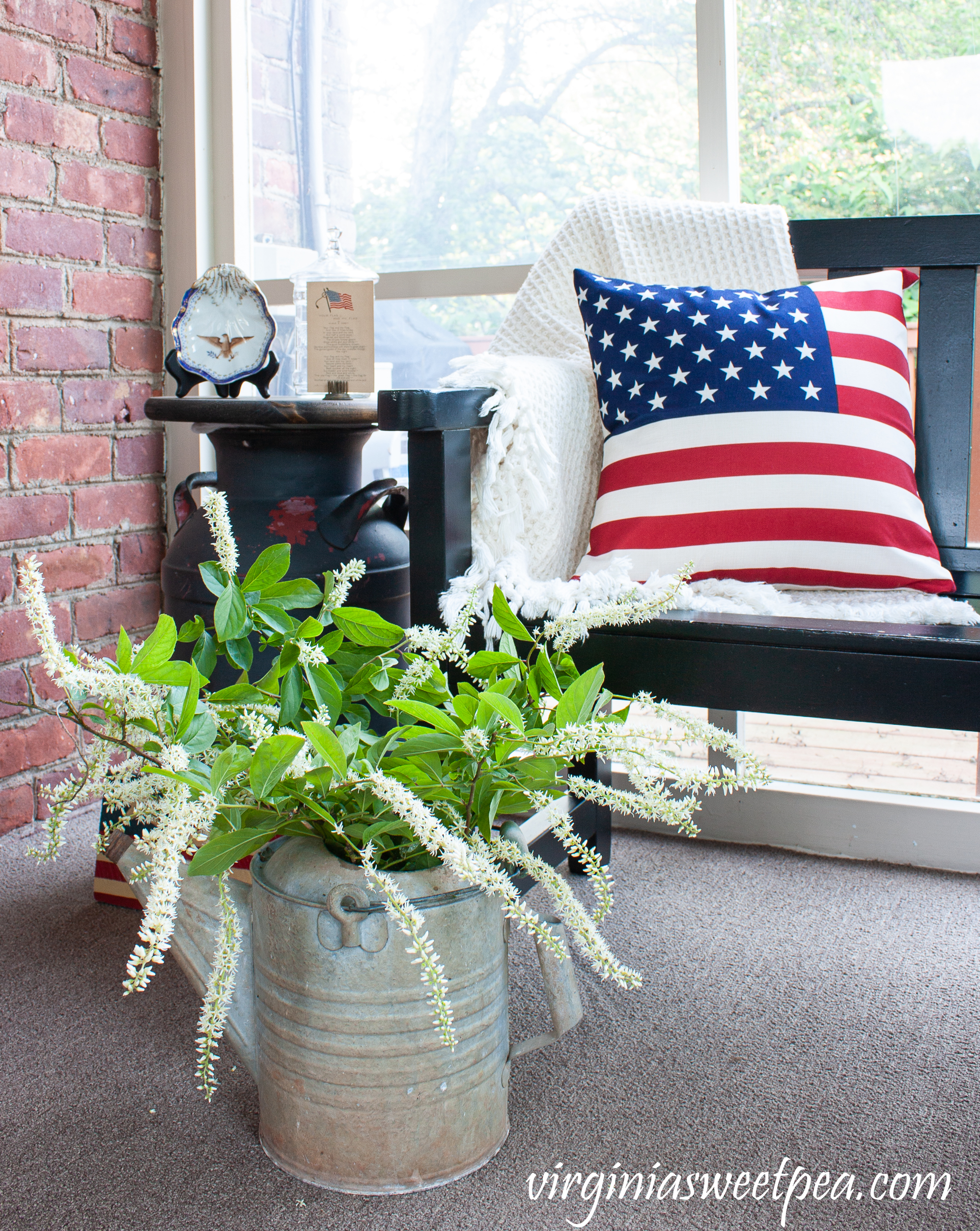 Patriotic porch decor with an American flag pillow and a vintage watering can filled with Virginia Sweetspire.